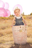 Baby girl playing in basket with balloons — ストック写真