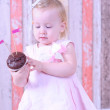 Baby girl with chocolate cupcakes — Stock Photo