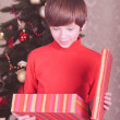 Surprised child opening christmas presents — Stock Photo