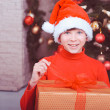 Cute boy holding christmas gift in room — Stock Photo