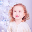Cute smiling baby girl holding christmas ball indoors — Stock Photo