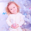 Cute smiling baby gitl sitting with christmas ball — Stock Photo