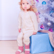 Cute baby girl sitting under christmas tree — Stock Photo