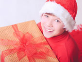 Smiling child holding christmas presents indoors — Stock Photo