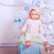 Cute baby girl sitting on christmas box in room — Stock Photo #35715741