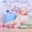 Cute baby girl lying under christmas tree — Stock Photo