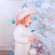 Laughing baby girl holding christmas ball in room — Stock Photo