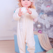 Happy baby girl in pajamas with christmas ball  — Stock Photo