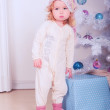 Cute baby girl in pajamas with christmas tree — Stock Photo