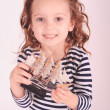Cute little girl holding toy ship in studio — Stock Photo #38389145