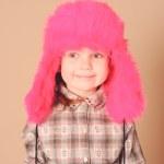 Smiling baby girl wearing fur hat in studio — Stock Photo #38496207
