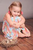 Baby girl with bird nest — Stock Photo