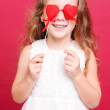 Stok fotoğraf: Smiling little girl playing with valentine's hearts