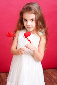 Cute little girl holding valentine's hearts — Stock Photo