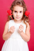 Cute girl holding valentine's hearts — Stock Photo