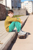 Boy sitting on skateboard — Stock Photo