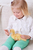 Girl sitting with duckling — Stock Photo