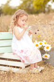 Girl sitting on boxes in meadow — Stock Photo