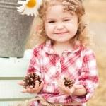 Girl holding pine cones — Stock Photo #48007089