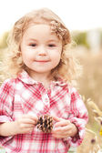 Girl holding pine cone — Photo