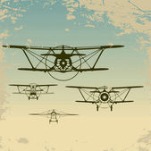 Old planes flying in the clouds, retro aviation background. — Stock vektor