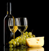 Bottle of wine, a bunch of white grapes and a piece of cheese — Stock Photo