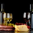 Wine, grapes, cheese and sausage on black background — Stock Photo