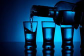 Vodka poured into a glass with glasses lit with blue backlight — Stock Photo