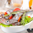 Stock Photo: Redfish on kitchen table with vegetables and spices