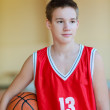 Basketball player with a ball in his hands and a red uniform. Basketball player practicing in the gym — Stock Photo