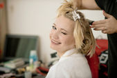 Hairdresser with a client at beauty salon. girl doing hairstyle — Stock Photo
