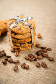 Biscuits, cinnamon sticks and coffee beans lying on sackcloth — Stock Photo