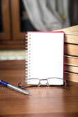 Notebook, a stack of books, glasses and pen — Stok fotoğraf