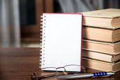 Notebook, a stack of books, glasses and pen — Stock Photo