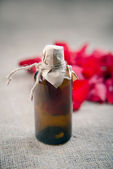 Essential oil bottle and red roses, perfume water — Stock Photo