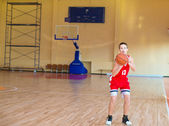 Basketball player with a ball in his hands and a red uniform. — Stock Photo