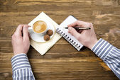 Man drinking coffee with chocolates — Stock Photo