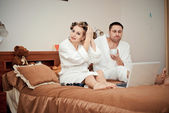 Young couple working on the computer in bed — Stock Photo