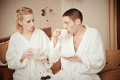 Man and woman drinking coffee in the morning in bed. — Stock Photo