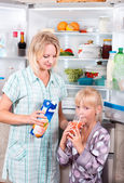 Young mother with a child takes food out of the fridge. — Stock Photo
