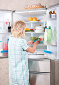 Young beautiful girl takes food from the refrigerator. — Stock Photo