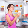 Young beautiful girl takes food from the refrigerator. — Stock Photo #42213169