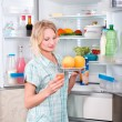 Young beautiful girl takes food from the refrigerator. — Stock Photo #42213219
