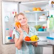 Young beautiful girl takes food from the refrigerator. — Stock Photo #42213225