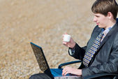 A man working on a computer outdoors. — Stock Photo