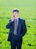 Happy young man speaks on a mobile phone outdoors — Stock Photo