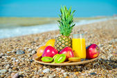 Plate of fresh fruit on the beach — Stock Photo