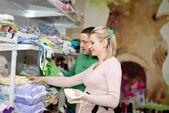 Mujer embarazada comprando ropa de bebé en supermercado. joven embarazada eligiendo ropa recién nacido — Foto de Stock