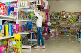 Kobieta w ciąży zakup odzieży dla dzieci w supermarkecie. młoda kobieta w ciąży wybierając ubrania noworodka — Zdjęcie stockowe