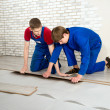 Young handsome men laid laminate floor covering, perform repairs — Stock Photo #48583743